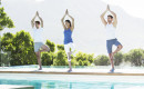 Men and woman practicing yoga at poolside